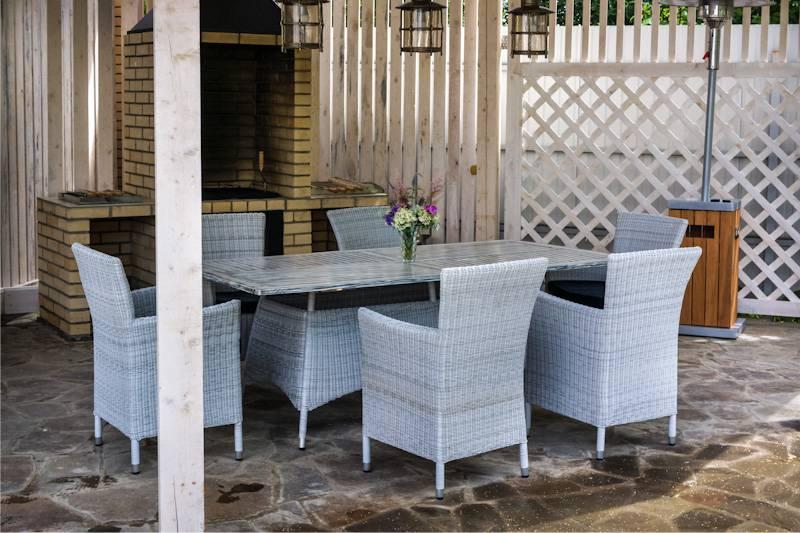 שולחן וכיסאות עשויים פלסטיק נצרים מתחת לעץ