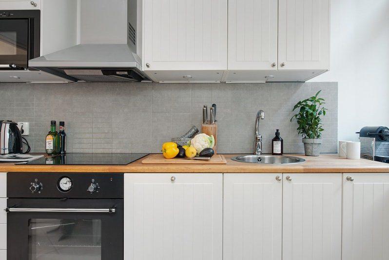 Kötény a nem szabványos téglalap alakú csempékből egy modern konyhabelsőben