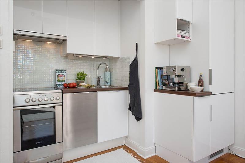 Küçük bir mutfağın iç kısmındaki ankastre buzdolabı