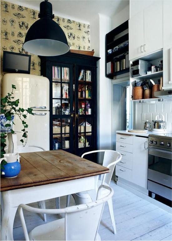 Móveis pretos e papel de parede amarelo no interior da cozinha