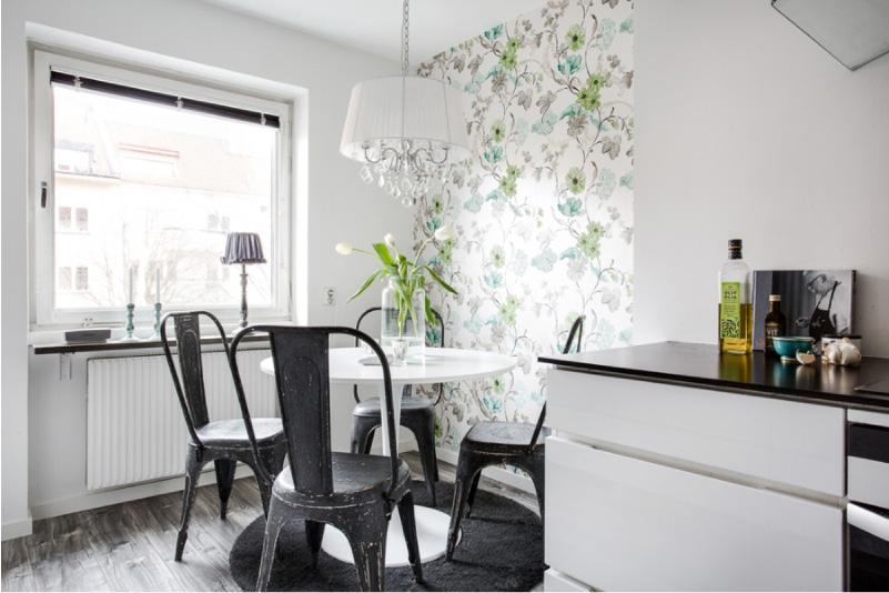 Cozinha preto e branco com papel de parede branco com cores verdes e azuis.
