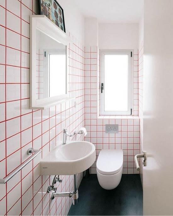 Coutures rouges et carreaux blancs dans les toilettes
